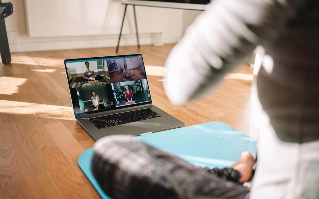 Profesora freelance dando clase online bonificadas de yoga a través de una videoconferencia.